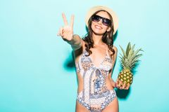 Summer tropical positive portrait of young pretty woman having fun, wearing bright bikini holding pineapple on green background. Summer tropical positive stock photography