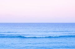 Summer tropical seascape with wave pastel tone water and sunset or sunrise sky in Samui - Thailand. Wide summer tropical seascape with wave pastel tone water and royalty free stock images