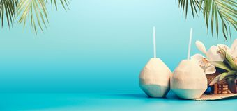 Summer tropical vacation background banner with fresh tropical coconut cocktails , drinking straws and hanging palm leaves on blue. Turquoise background. Travel stock photos