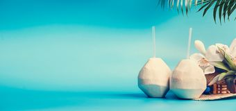 Summer tropical vacation background banner with fresh tropical coconut cocktails , drinking straws and palm leaves and flowers. Standing on blue turquoise royalty free stock image