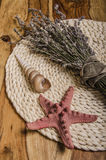 Summer trove. Souvenirs from the country and the seaside - dried lavender boquet, shells and the starfish lying on the wooden background Stock Photography