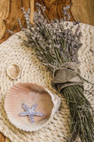 Summer trove. Souvenirs from the country and the seaside - dried lavender boquet, shells and the starfish lying on the wooden background Royalty Free Stock Image