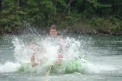 Summer Tubing. Young man riding a tube in a lake, splashing heavily Stock Image