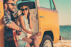 Summer tunes. Happy young couple enjoying time together while sitting in their retro minivan with sea in the background Royalty Free Stock Photo