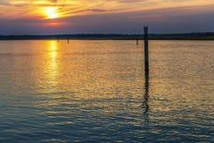 Summer twilight over the lagoon shoreline in Bibiobe, venice. Summer sunset over the lagoon water and shoreline inside Bibione, Venice royalty free stock image