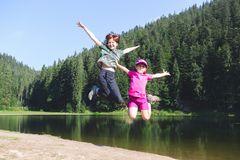 Happy family  at the lake Synevyr. Summer - two sisters on a hike. Fun happy family  jumping on the shore of a mountain lake synevyr royalty free stock photos