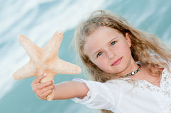 Summer vacation. Beautiful girl with starfish at the beach Stock Photo