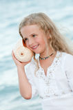 Summer vacation. Beautiful girl with seashell at the beach Stock Image