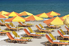 Summer vacation. Colorful yellow-orange sun chairs and umbrellas arranged in rows. Sea represents as a contrast background. Horizontal image Stock Images