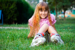 Summer vacation. A young girl to skate resting in the park Royalty Free Stock Photography