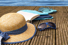 Summer vacation, accessories for beach holidays as straw hat, fl. Ip flops, blue sunglasses, turquoise towels and a book on a wooden bathing jetty right on the Royalty Free Stock Image