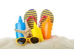 Summer vacation accessories in clear sea sand isolated on white background. Summer vacation stock photo