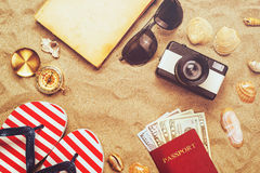 Summer vacation accessories on tropical sandy ocean beach, holidays abroad. Summertime lifestyle objects and US American dollars in flat lay top view stock photo