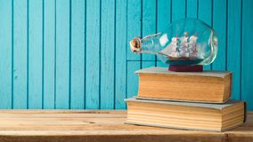 Boat and books on wooden table Stock Images