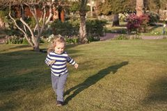 Summer vacation, adventure, discovery. Boy with blond hair run on green grass. Activity, experience, learning. Happy childhood concept. Child in blue clothes royalty free stock photos