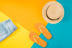 Summer vacation background with orange flip flops, denim trousers and hat Royalty Free Stock Photography