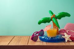 Summer vacation background with orange juice, beach accessories and pool float. On wooden table royalty free stock photography