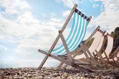 Summer vacation deck chairs on the beach at the seaside Stock Images