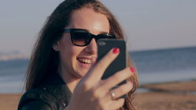 Summer vacation beach travel. Technology and people concept with smiling woman making selfie with smartphone on beach stock footage