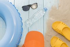 Summer vacation on the beach. Yellow flip-flops and swimming circles, bottle and sunglasses. Summer vacation on the beach. Yellow flip-flops and swimming royalty free stock images