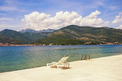 Summer vacation. Beautiful landscape with one chaise lounge on beach. Montenegro, Bay of Kotor. Adriatic Sea, Tivat stock images