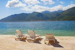 Summer vacation. Beautiful sunny landscape with chaise lounges on beach. Montenegro, Adriatic Sea, view of Bay of Kotor. Summer vacation. Beautiful sunny stock photography