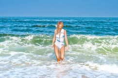 Summer. Beautiful tanned woman in swimsuit is coming out of the. Summer vacation. Beautiful tanned woman in swimsuit is coming out of the ocean on tropical beach stock photography
