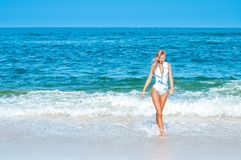 Summer. Beautiful tanned woman in swimsuit is coming out of the. Summer vacation. Beautiful tanned woman in swimsuit is coming out of the ocean walking on stock image