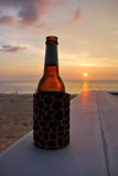 In a summer vacation. Bottle of beer on the beach at sunset Stock Image