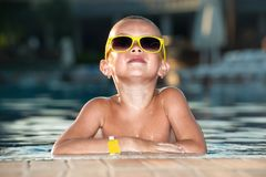 The boy with sunglasses resting in the pool.Summer vacation. stock photos