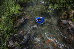 Summer Vacation, Boy Tubes on River Telluride, Colorado. A boy in an inner tube drifts down a crystalline mountain stream in Telluride, Colorado Royalty Free Stock Photography
