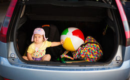 Summer vacation car luggage. Funny image with baby sitting in car trunk full of luggage, going in summer vacation Royalty Free Stock Image