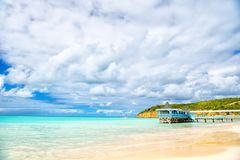 Summer vacation on caribbean. Sea beach with wooden shelter in antigua. Pier in turquoise water on cloudy sky background. Wanderlu Stock Image