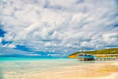 Summer vacation on caribbean. Sea beach with wooden shelter in antigua. Pier in turquoise water on cloudy sky background. Wanderlust, travel, trip. Adventure stock images