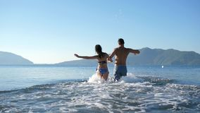 Summer vacation, cheerful man with woman holding hands run to swim at sea stock video