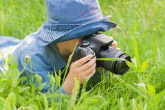 Summer vacation. Children's pleasure. The child learns to love the nature. To lie on a grass. To hold a camera in hand. In the open air. Children's walk. For Stock Photo