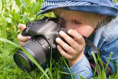 Summer vacation. Children's pleasure. The child learns to love the nature. To lie on a grass. To hold a camera in hand . In the open air. Children's walk . For Stock Photos