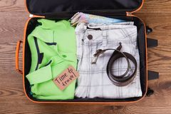 Summer vacation clothes and accessories for traveling. Folded male apparel in suitcase Stock Image