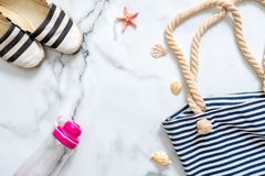 Summer vacation composition. Elegant sandals, striped beach bag, seashells, sea star, water bottle on marble background. Women`s stock image