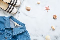 Summer vacation composition. Fashionable jeans jacket, striped summer sandals, seashells, sea star on marble background. Women`s d stock photo