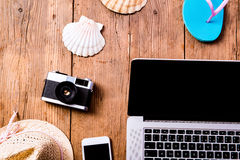 Summer vacation composition. Laptop, camera, hat, shell, flip fl. Summer vacation composition with laptop, camera, smart phone, blue flip flop sandals, hat and stock images