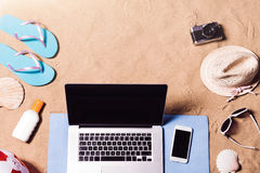 Summer vacation composition. Sandals, hat, laptop and smartphone Stock Photos