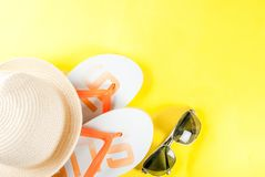 Summer vacation concept. Bright yellow background with hat, sun glasses and flip flops Royalty Free Stock Photo