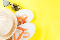 Summer vacation concept. Bright yellow background with hat, sun glasses and flip flops Royalty Free Stock Photos