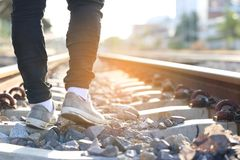 Summer vacation concept, Closeup of Man sneaker shoes walking at train station on evening sunset light stock photos