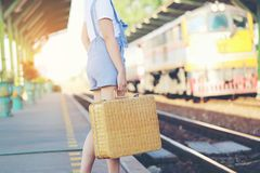 Summer vacation concept, Closeup of woman holding brown natural wicker bag at train station on evening sunset light, Fashionable stock photo