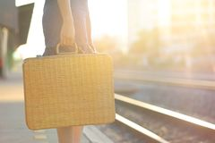 Summer vacation concept, Closeup of woman holding brown natural wicker bag at train station on evening sunset light, Fashionable royalty free stock image