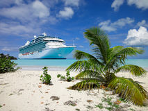 Summer vacation concept with cruise ship and beach. Cruise ship anchored close to a tropical beach in the Caribbean Sea. Small palm tree in the front Royalty Free Stock Photography