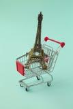 Summer vacation concept. Eiffel Tower souvenir inside shopping cart Stock Photos