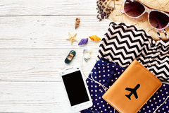 Summer vacation concept flat lay. colorful retro swimsuit, hat s. Unglasses and shells passport and phone  on white wooden background, top view. space for text Stock Photo